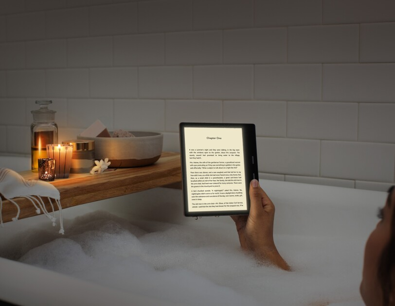 A woman relaxes in a bubble bath while reading a Kindle Oasis in candle lighting.