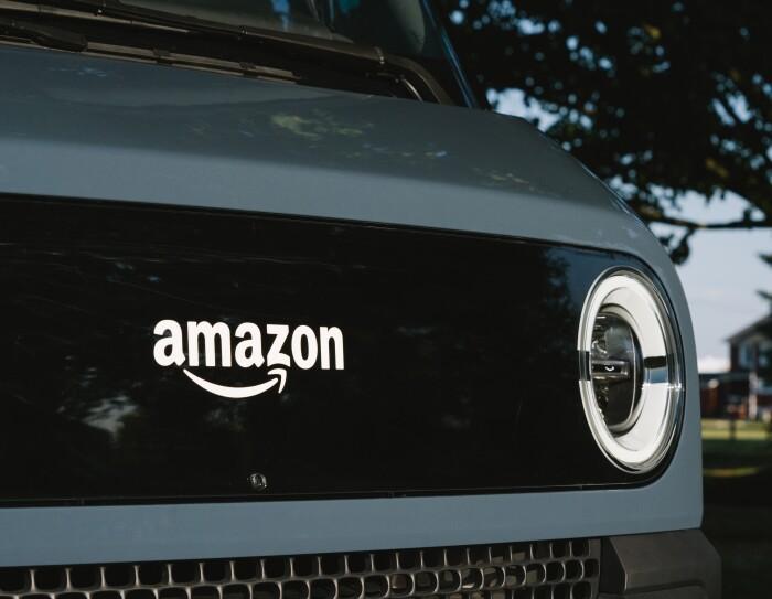 Primo piano del fronte del furgone Rivian, con il logo Amazon al centro e un fanale del furgone sulla destra