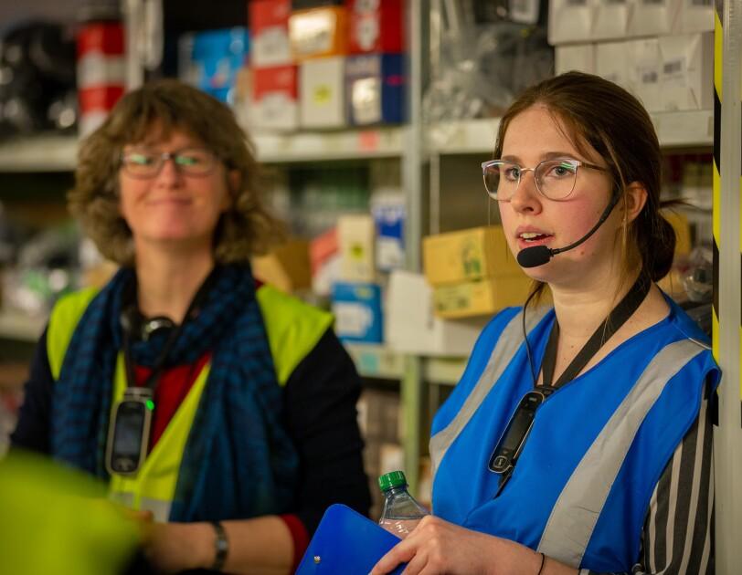 Im Bildvordergrund: Eine junge Frau mit Brille, Headset und blauer Weste. Links neben ihr (etwas unscharf) erkennt man eine Besucherin in gelber Sicherheitsweste.