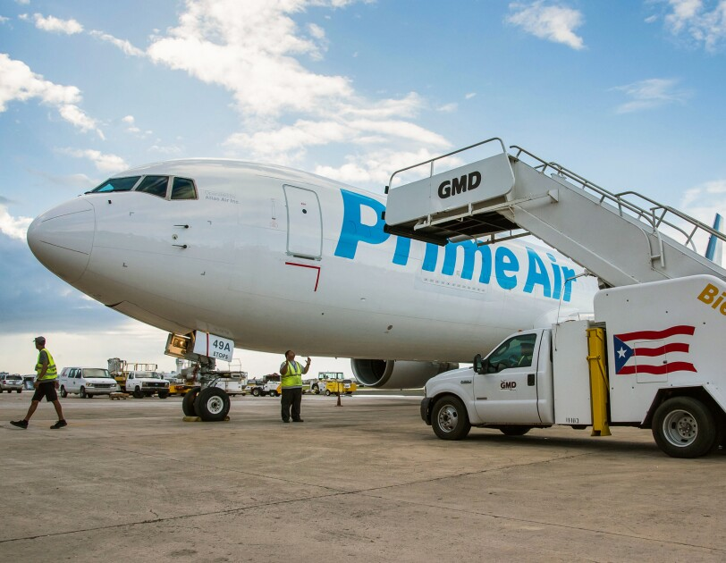 """Ground crews approach an airplane on a tarmac. The plane says """"Prime Air"""" on the side."""