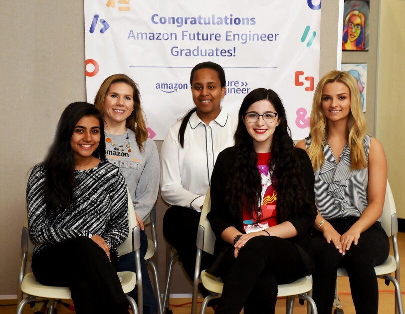 "Five young women sit on chairs, smiling at the camera, as they sit in front of a poster that says ""Congratulations Amazon Future Engineer Graduates."""