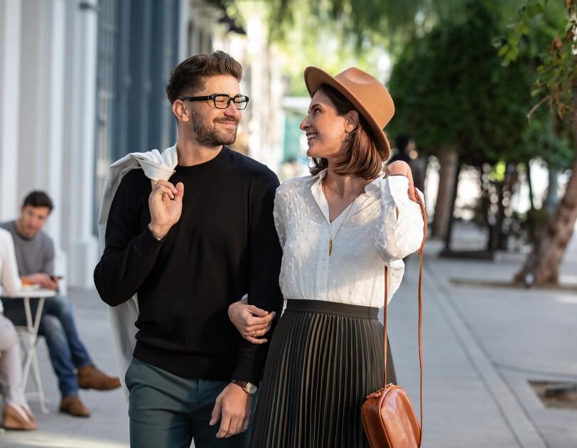 A man and woman walk down the street. He wears Echo Frames.