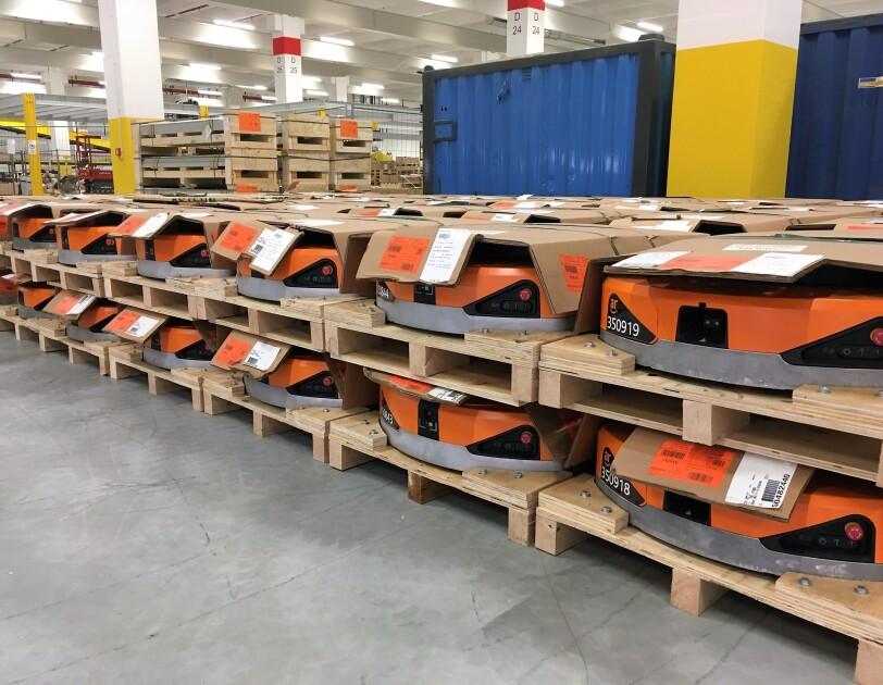 Auf Paletten stapeln sich orange-farbene Amazon Transportroboter. Sie ähneln haushaltsüblichen Saugroboter, sind aber deutlich größer.