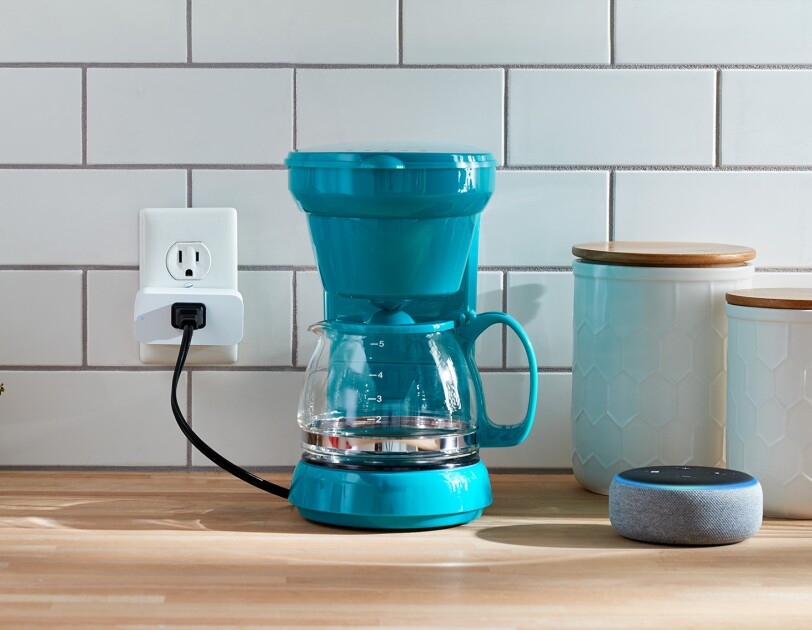Amazon Smart Plug in a kitchen setting. It's plugged into an outlet, with a coffee pot plugged into it. To the right is a new Echo Dot device, and two stoneware storage containers. To the left is a potted plant, a coffefe pot and hand towel.