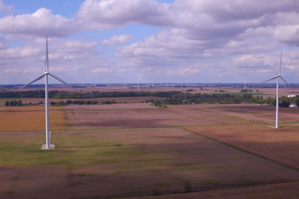 Multiple wind turbine sits in fields of crops at the Amazon Wind Farm Indiana – Fowler Ridge.