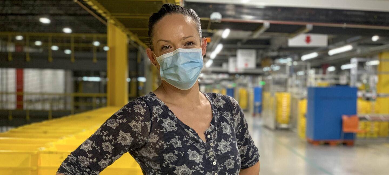 Una asociada está dentro del centro logístico. Lleva mascarila azu l, un jersey azul estampado con unoz dibujos de color blanco. Las mano las tiene en la cintura. De fondo cajas de color amarillo y azul.