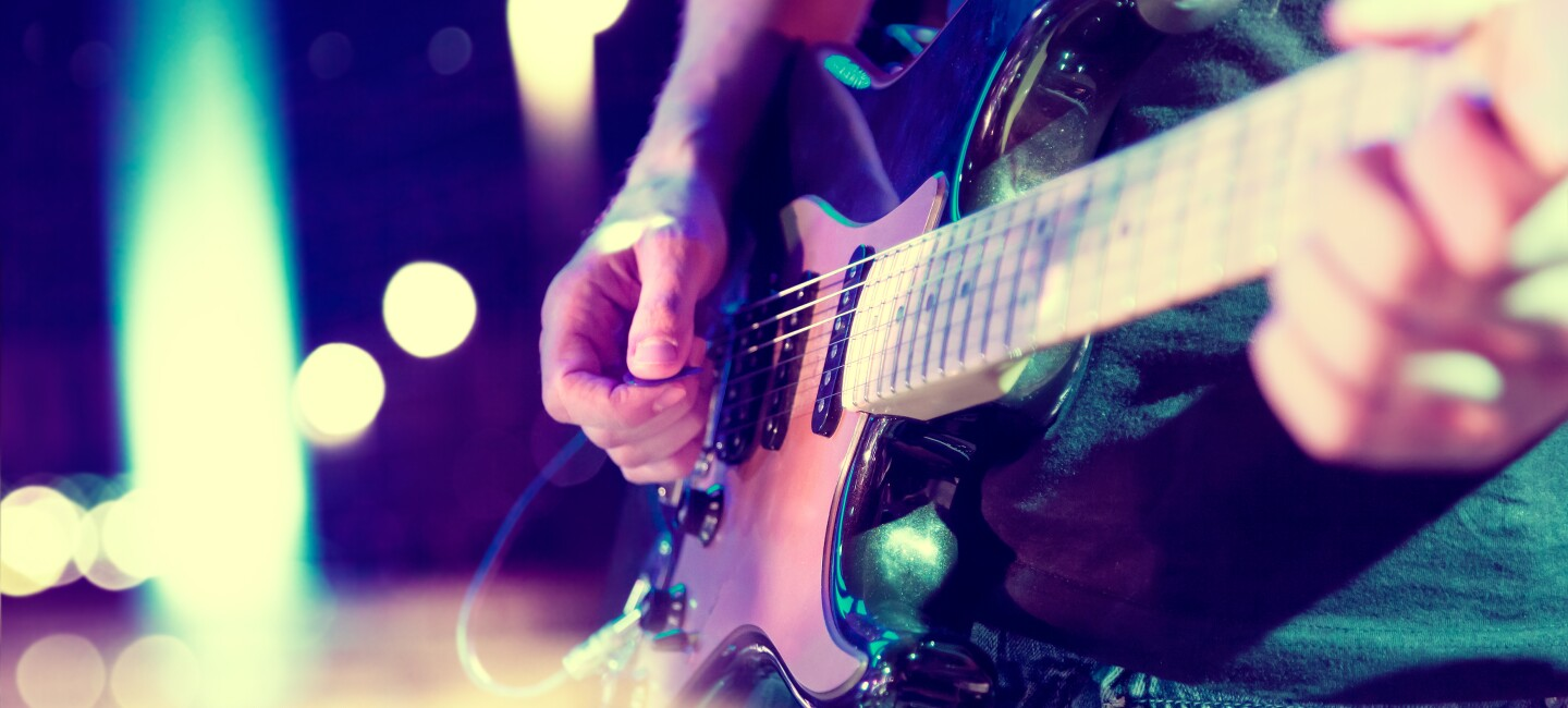 Close-up image of a man playing an electric guitar, with lights blurred out in the background.