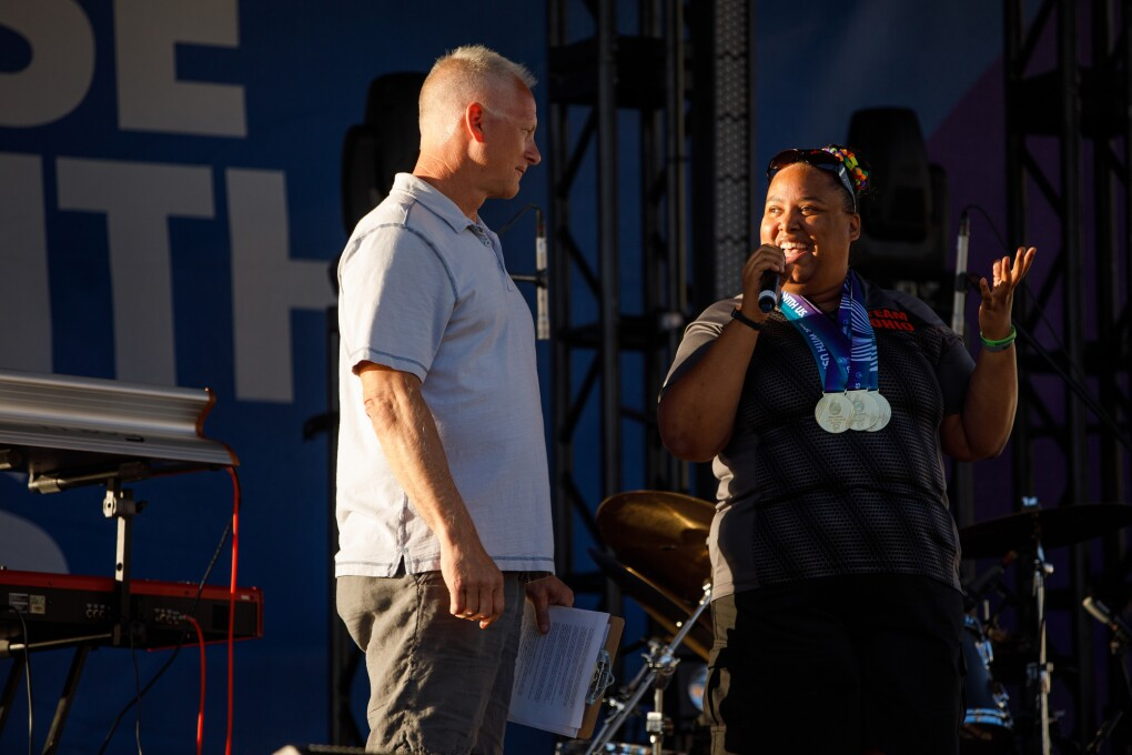 On stage, ESPN's Kenny Mayne appears to be readying to take the microphone to speak during the USA Games closing ceremony. Next to him, Special Olympian Ali Riddick is speaking to Mayne and the audience, while wearing medals from the Special Olympics.