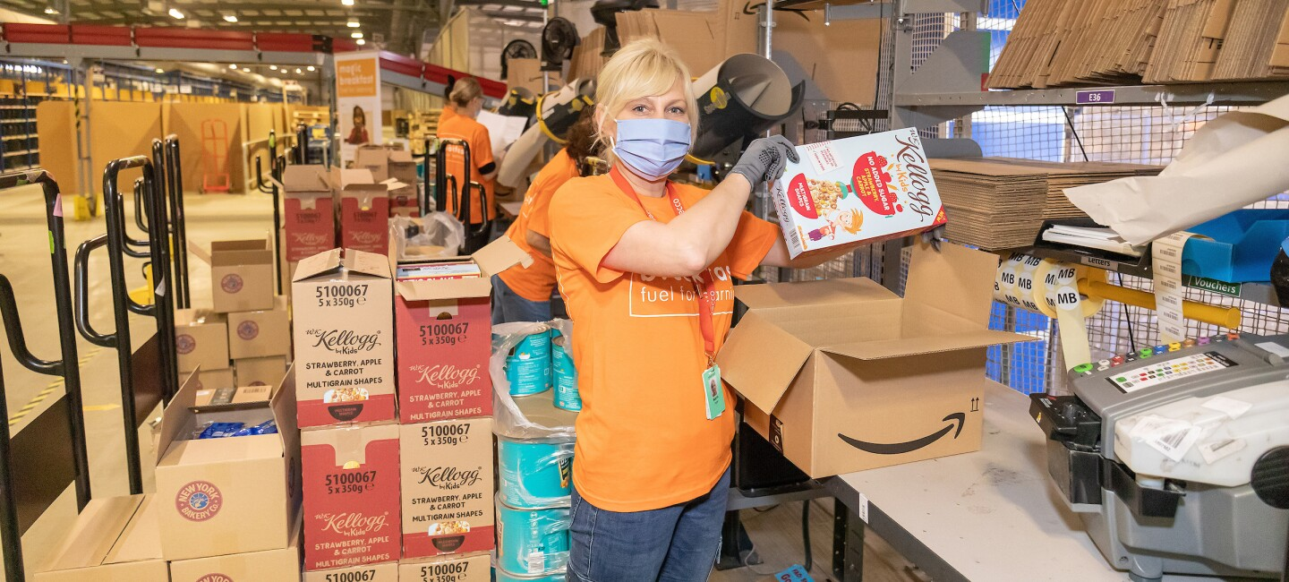 Lady packing cereal into an Amazon box to send out for Magic Breakfast - to children across the country