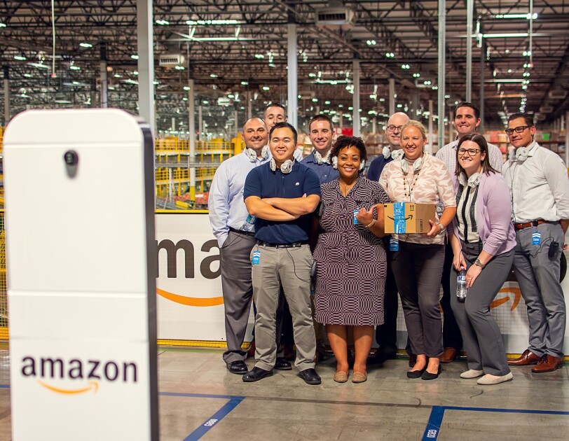 A group of people pose in front of a camera built into a stand marked with the Amazon smile logo.