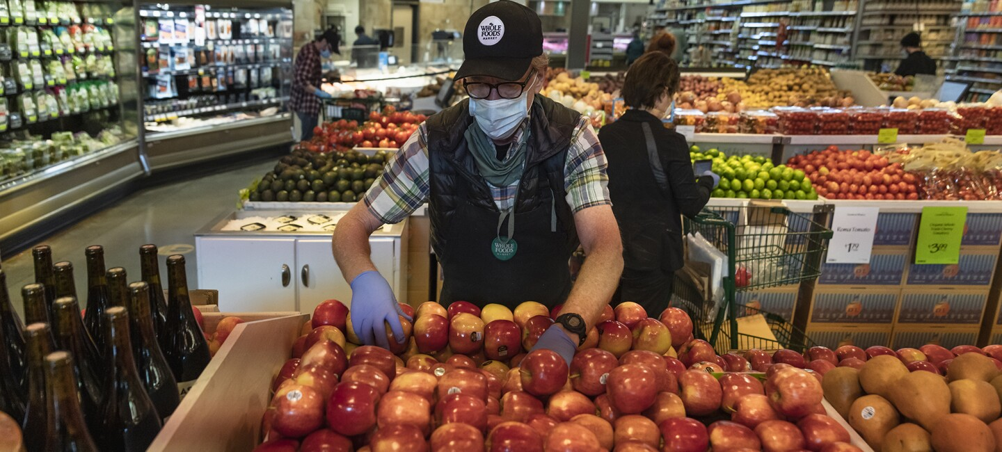 A Whole Foods Market Team Member organizes apples in the grocery store.