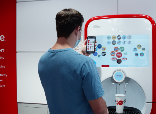 A man wearing a mask while standing in front of a Coca-Cola Freestyle machine uses his mobile phone to select and pour his soda in a touchless experience.