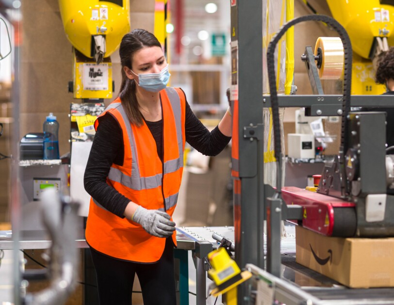 Amazon employee in mask and gloves using tape machine