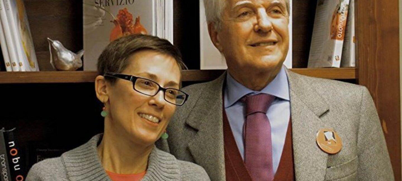 Ritratto di Gianpiero Zazzera e di sua moglie Liz, proprietari di Bibliotheca Culinaria. Sullo sfondo alcuni scaffali con dei libri.