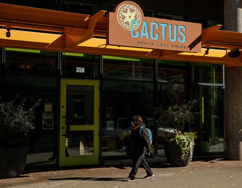 "A pedestrian wearing a medical mask passes a restaurant with ""CACTUS"" on its sign."
