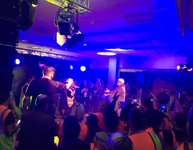 Auf einer von Scheinwerfern erhellten Bühne sieht man DJ Ötzi, dessen Blick auf einem Amazon Mitarbeiter gerichtet ist, der in ein Mikrofon singt. Sie sind umgeben von zahlreichen Logistikmitarbeitern, die von hinten zu sehen sind.