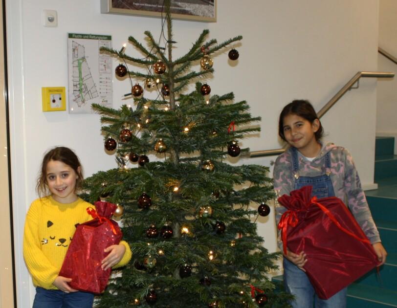 Zwei Kinder halten Geschenke in den Armen und stehen neben einem Weihnachtsbaum.