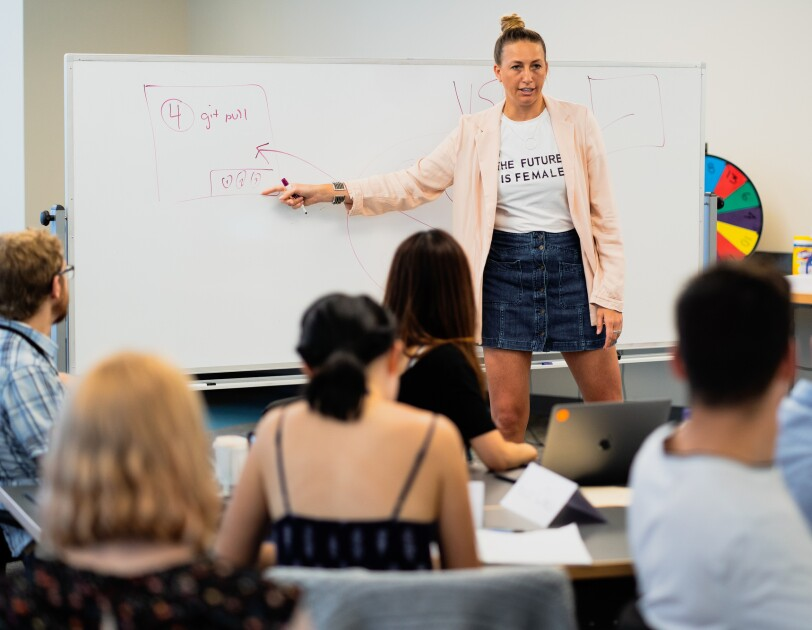 A woman stands at the front of a classroom and points to information on a whiteboard.
