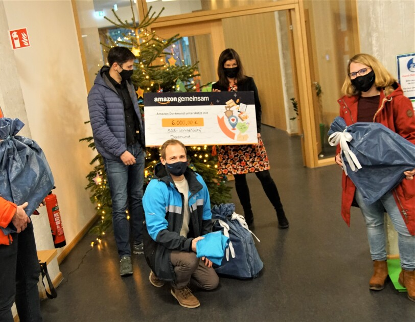 Verschiedene Personen vor einem Weihnachtsbaum mit spendenscheck