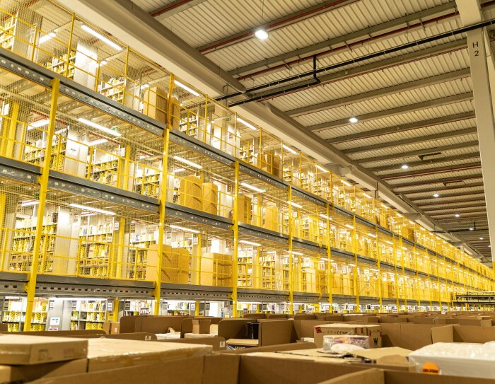 Cenrto logístico de San Fernando de Henares. En primer plano aparecen cajas de cartón llenas de productos y en el fondo una estantería amarilla de cuatro niveles.