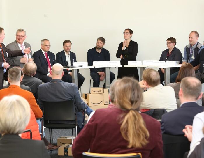 Bürgermeister Andre Wiese spricht vor mehreren Zuhörern und Teilnehmern der Podiumsdiskussion.