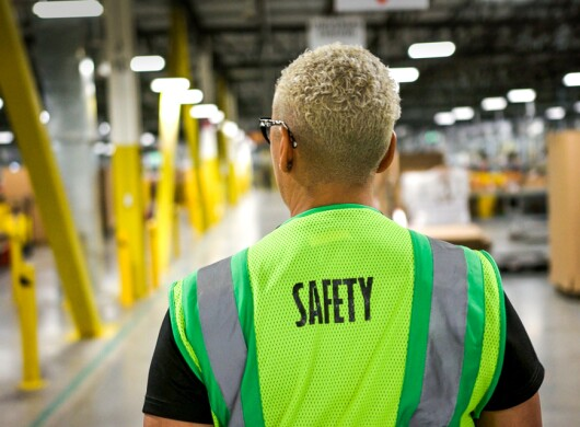 A person wearing a safety vest in a warehouse.