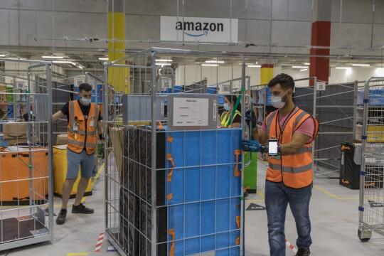 Un gruppo di dipendenti Amazon sposta dei carrelli contenenti dei pacchi. In alto sullo sfondo il logo di Amazon