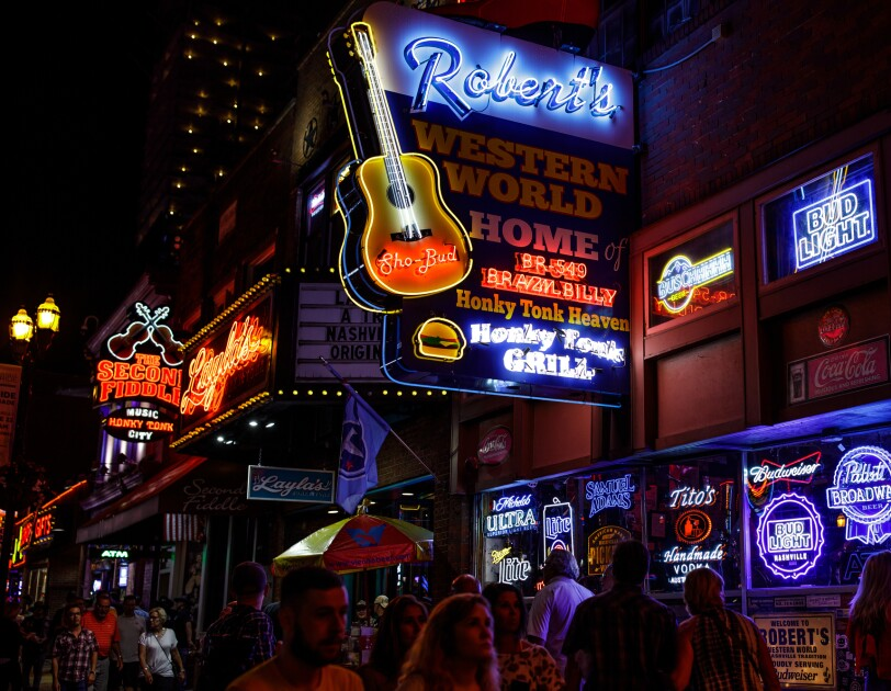 Nighttime street scene with many neon signs featuring country music imagery.