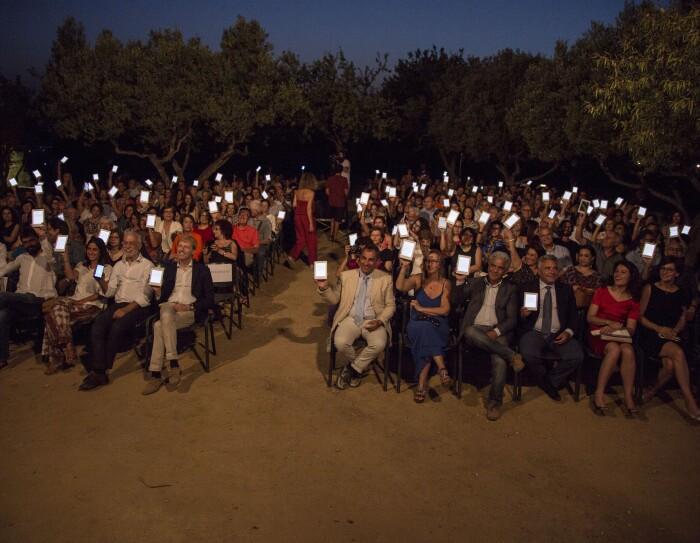 Platea di persone sedute nella Valle dei Templi di Agrigento durante un reading di Luigi Pirandello in occasione dei 150 della sua nascita. Gli spettatori reggono con una mano un Kindle PaperWhite, con lo schermo rivolto verso la camera. Sullo sfondo, degli alberi.
