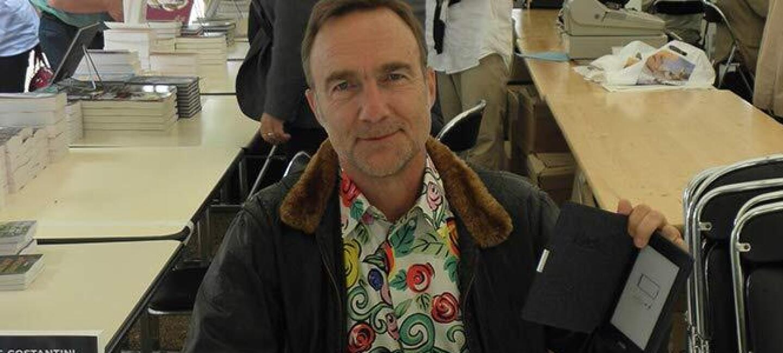 L'auteur autoédité sur KDP Chris Costantini est à assis à une table pour une séance de dédicaces et montre une liseuse Kindle d'Amazon en souriant