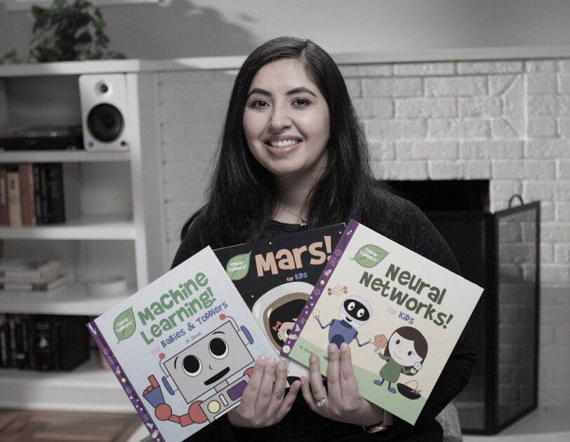 A woman holds three books for children that she self-published on KDP