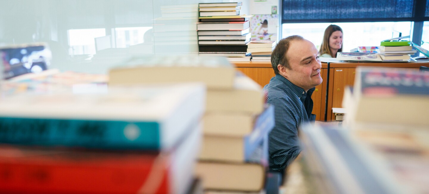 A seated man is mostly obstructed by stacks of books in the foreground of this image. He wears a dark button-down shirt and has brown hair. In the background is a woman with long brown hair as well as more stacked books on top of book shelves.