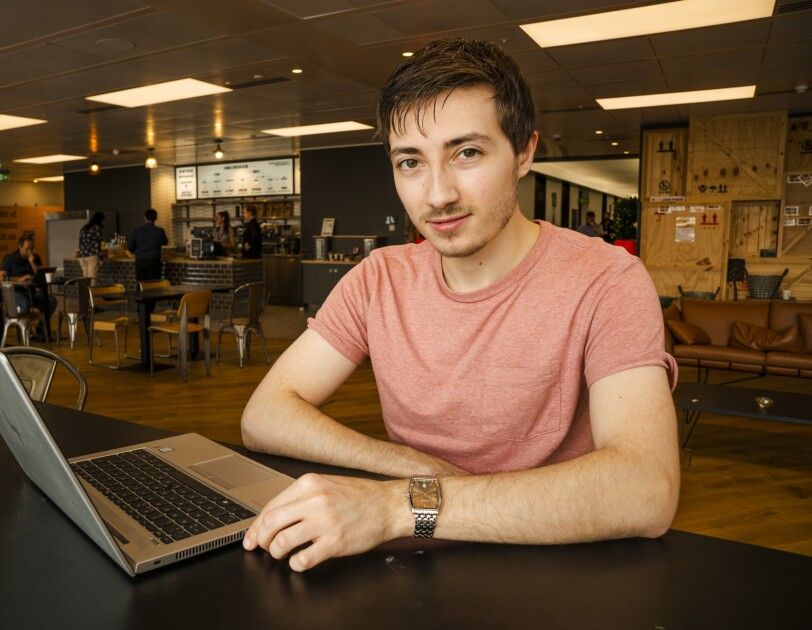 Jake Peters, 23, an  Infrastructure Technician apprentice sitting in the UK Amazon corporate office cafeteria behind a laptop.