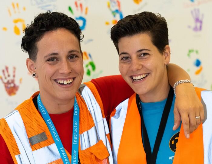 María García y Susana Torres fueron dos de las afortunadas que disfrutaron del desfile del Día del orgullo LGTBI desde la carroza de glamazon. la dos visten con los chalecos naranjas de Amazon y miran a cámara sonriendo. Tienen el pelo corto y pendientes. María abraza a su pareja del cuello.