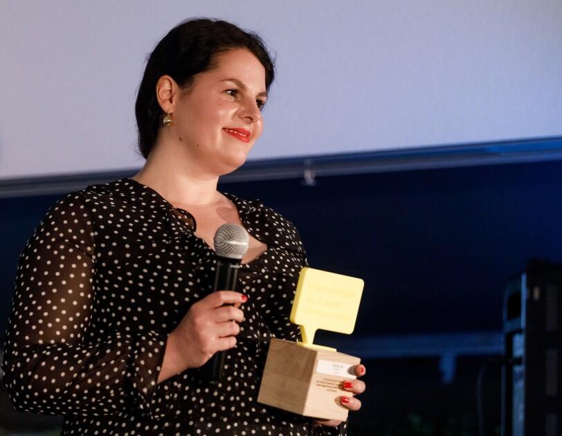 Julia Ritte hat den Preis steht auf der Bühne. In einer hand hält sie ein Mikrofon, in der anderen den UdZ-Pokal. Sie blickt freundig und gerührt ins Publikum.