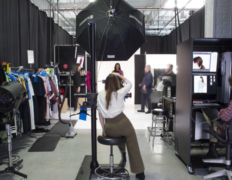An Amazon Fashion photographer, in a white shirt and brown slacks, photographs a model at Amazon Fashion's studios.