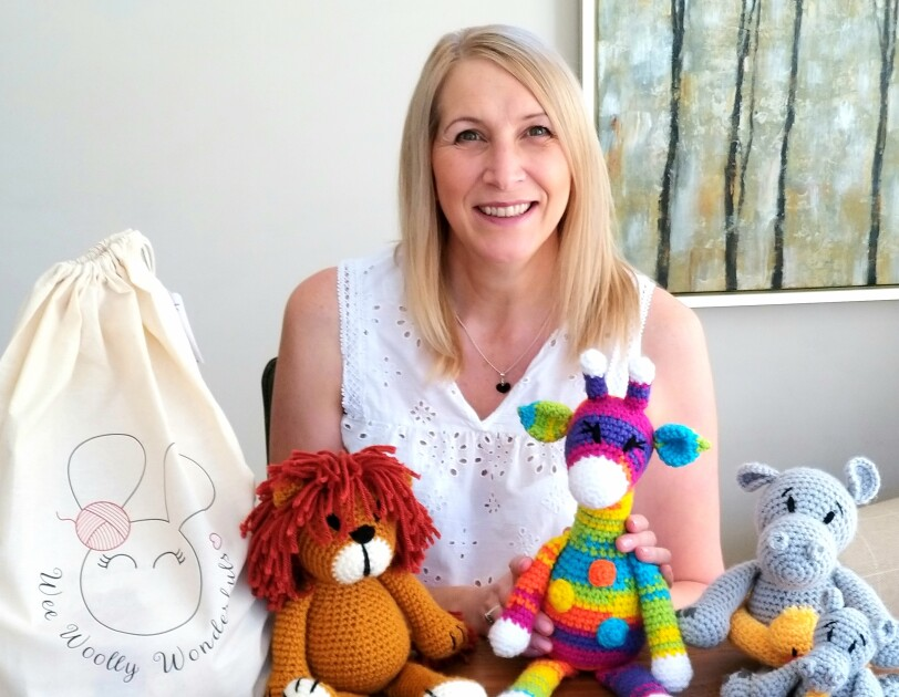 Lisa Dobbs from Wee Woolly Wonderfuls sitting behind some of the toys that she has made using her crochet kits.