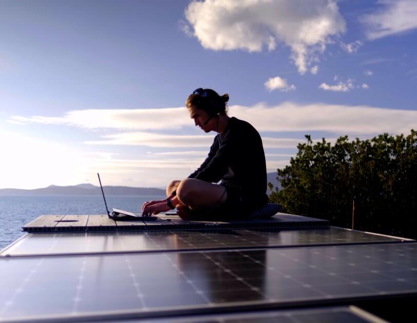 Ein Mann mit Laptop und Headet sitzt auf dem Camper Dach und tippt am Laptop. Im Hintergrund ist das Meer und die Berge zu sehen