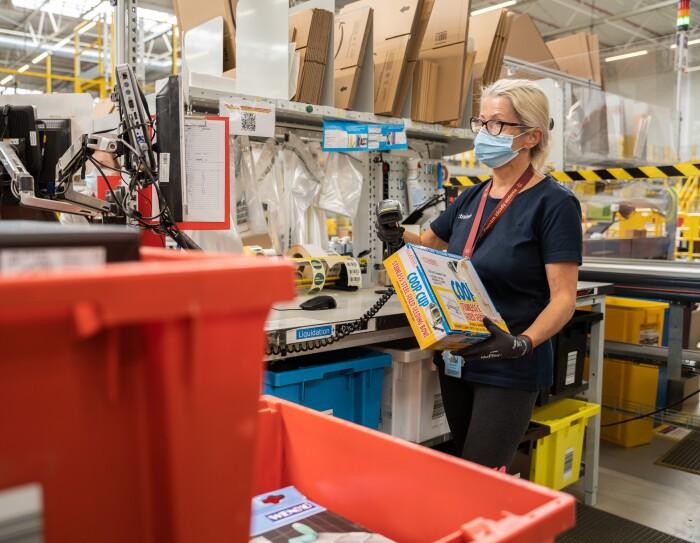 L'immagine mostra una dipendente amazon all'interno del magazzino che controlla i prodotti resi