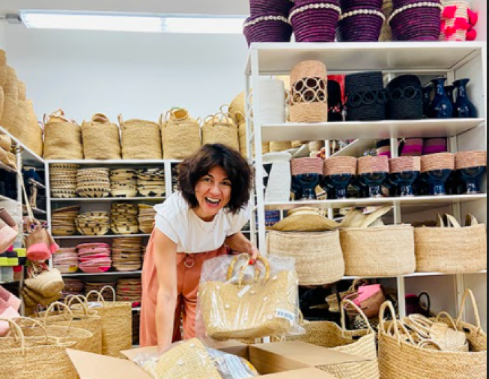 A smiling woman with woven baskets places them into a cardboard box.