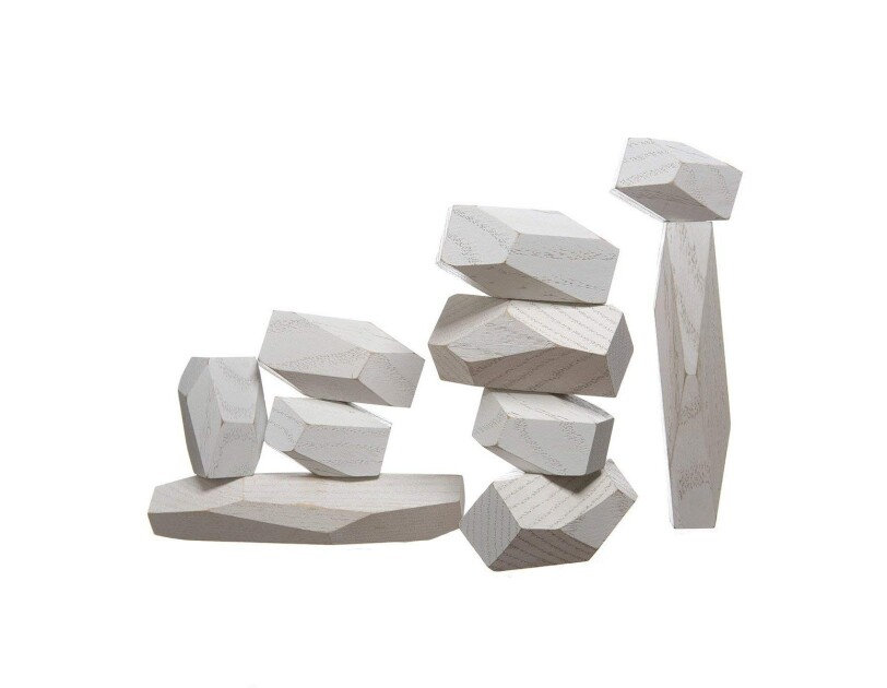 A stack of four balancing blocks  next to a taller stack of a vertical block, topped with 5 additional wood blocks, all of varying shapes and sizes.
