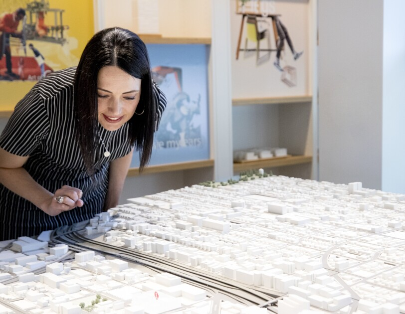 A woman in a grey-striped shirt stands over a scale model of the South Lake Union neighborhood.