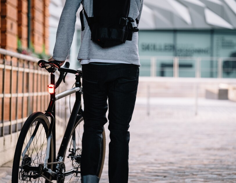 Cyclist stood with his back to camera holding a bike