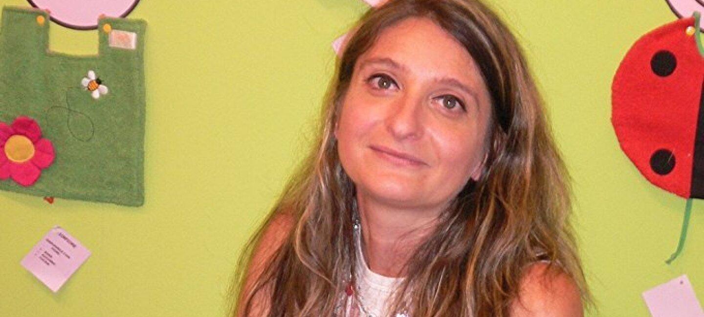 Ritratto di Luisa Masciello, venditrice di bavaglini su Amazon. La donna sorride verso la camera, seduta di fronte al suo laptop. Sullo sfondo un muro verde con alcuni dei suoi prodotti appesi.