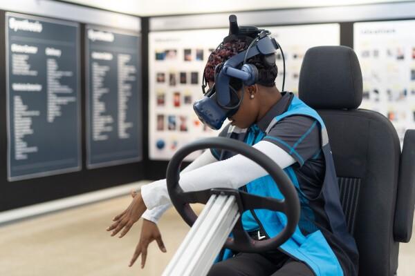 Donna indossa un visore per realtà virtuale mentre è seduta su una poltrona con un volante di fronte a sè.
