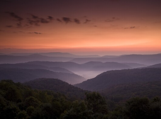 Sunset over a mountain range. The sky is a vibrant shade of orange. The mountains are dark with a light layer of fog resting over them.