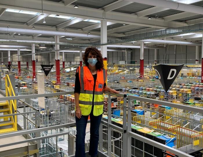 Donna in piedi su un piano rialzato in un centro operativo Amazon. Indossa una mascherina chirurgica, ha i capelli neri.