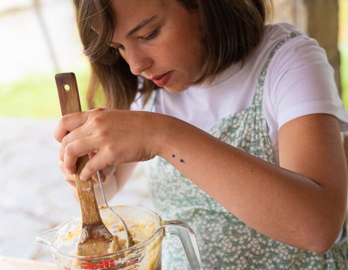 María Gómez Iribarnegaray mezclando los productos naturales para crear un jabón sólido.  María mezclando en la terraza de casa de su abuela en Villasana de Mena. En un recipiendo de cristal y encima de una table de madera, en una mano una pala de madera u en la otra de cristal.