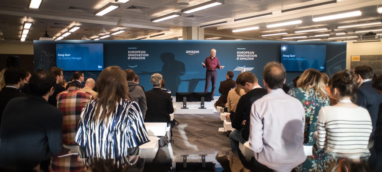 Celebración del Día Europeo de la Innovación 2018. Doug Gurr, Country Manager de Amazon.co.uk aparece en el fondo de la foto presentando el evento. Está de pie y viste una camisa morada y unos pantalones negros. Su audiencia se encuentra de espaldas a la foto. Detrás de él, un panel azul con el título del evento Día Europeo de la Innovación.