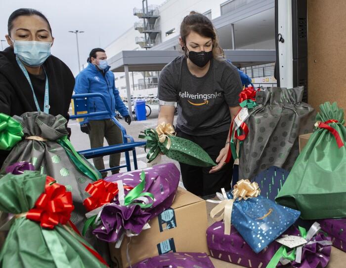 Dos trabajadores de Amazon cargando una furgoneta para realizar la donación a Fundación Acogida (Madrid). Se ve la furgoneta desde dentro y en la puerta trasera hay dos chicas organizando regalos que van en bolsas de diferentes colores: verde, gris, morado y azul. Las dos chicas est´´an situadas en la puerta trasera de la furgoneta. La de la izquierda lleva mascarilla azúl y sudadera negra. La otra chica lleva el pelo recogido, mascarilla negra y camiseta de Amazon gris, manga corta, con la etiqueta DeliveringSmiles. De fondo se ve el conductor con mascarilla azul, chaqueta azul y pantalón gris. Y de fondo el exterior de un centro logístico de Amazon.